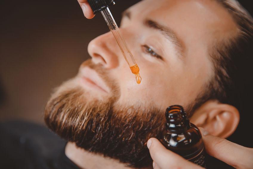Application d'une huile à barbe sur la barbe d'un homme